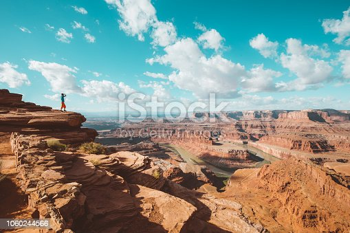 A young male hiker is standing on the edge of a cliff enjoying a dramatic overlook of the famous Colorado River and beautiful Canyonlands National Park in scenic Dead Horse Point State Park, Utah, USA