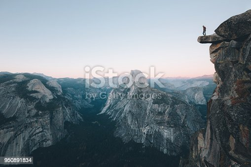 A fearless hiker is standing on an overhanging rock enjoying the view towards famous Half Dome at Glacier Point overlook in beautiful post sunset twilight, Yosemite National Park, California, USA Processed with VSCO with hb1 preset