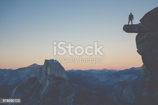 A fearless hiker is standing on an overhanging rock enjoying the view towards famous Half Dome at Glacier Point overlook in beautiful post sunset twilight, Yosemite National Park, California, USA