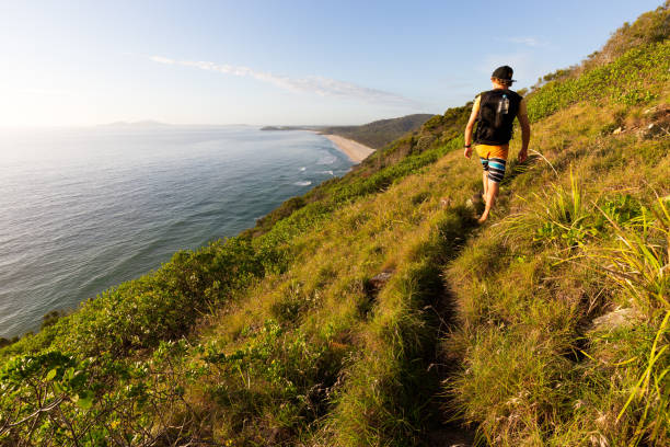 A Hiker on a Trail Looks Over a Coastal View stock photo