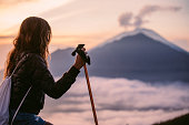 Young women hiker enjoying the view of Mt. Batur and Mt. Agung, Bali, Indonesia
