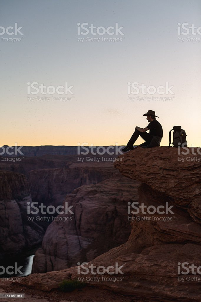Hiker on edge of Grand Canyon cliff in Arizona. stock photo