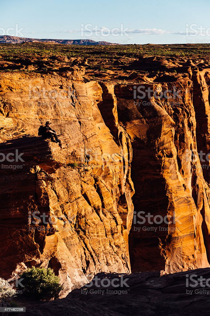Hiker on edge of Grand Canyon cliff in Arizona. stock photo