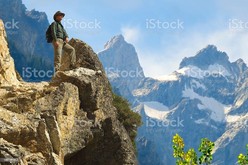Hiker on Ledge above Grand Tetons royalty-free stock photo