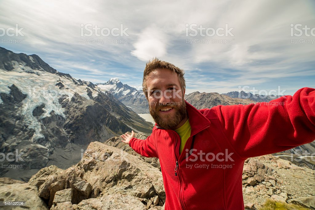 Hiker on mountain top captures achievement, Mount Cook on background stock photo