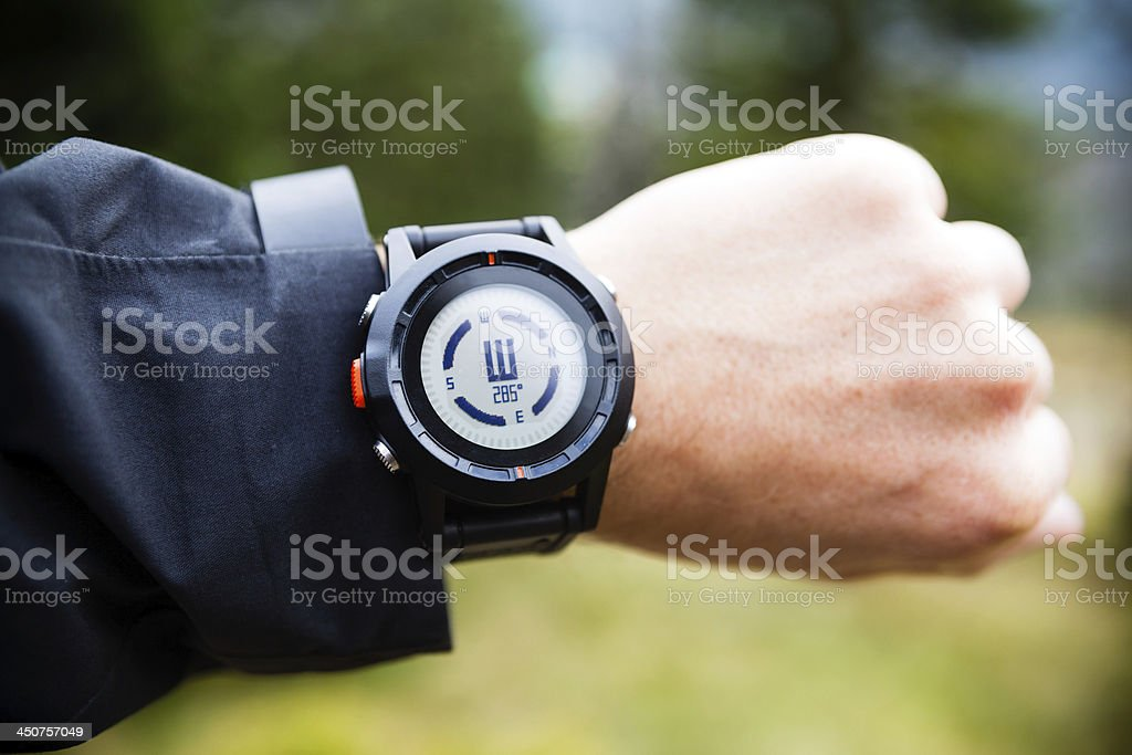 Hiker on mountain trail checking compass royalty-free stock photo