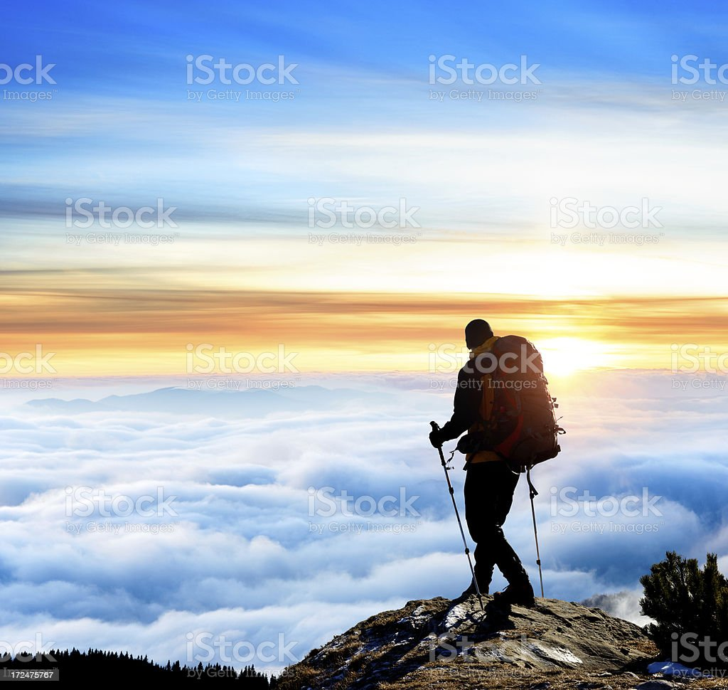 Hiker on mountaintop with clouds and sky backdrop stock photo