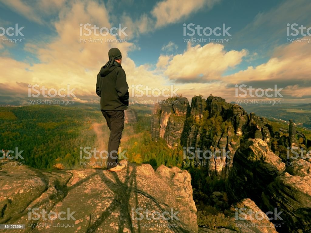 Hiker on rock end above valley. Man watch over misty and autumnal morning valley to bright morning nowhere. royalty-free stock photo