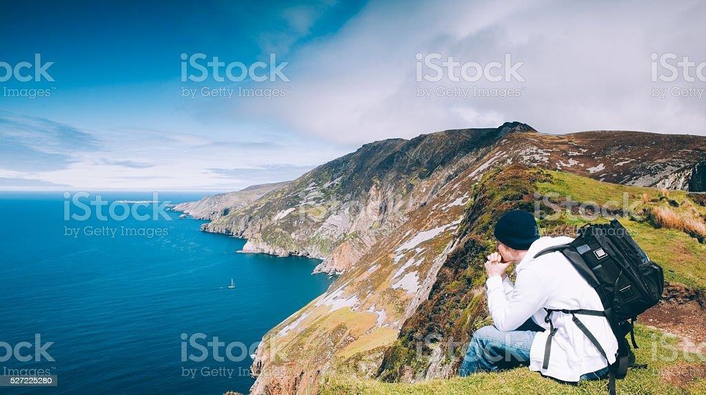 Hiker on Slieve League cliffs enjoys view of Atlantic ocean stock photo