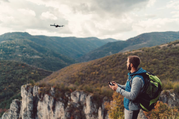 Hiker on the mountain top flying a drone to make videos and photos Tourist on the mountain flying a drone drone point of view stock pictures, royalty-free photos & images