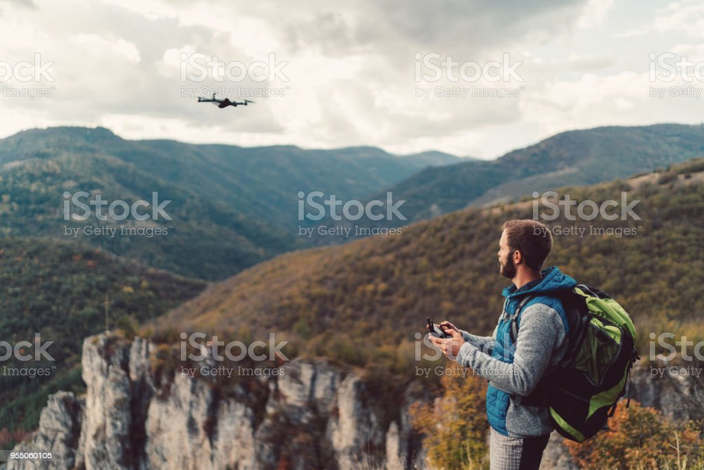 Hiker on the mountain top flying a drone to make videos and photos stock photo