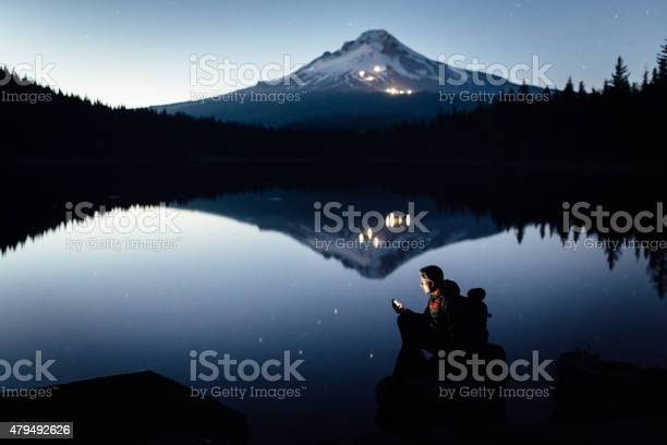 Photo of Hiker on the shore of the lake during twilight