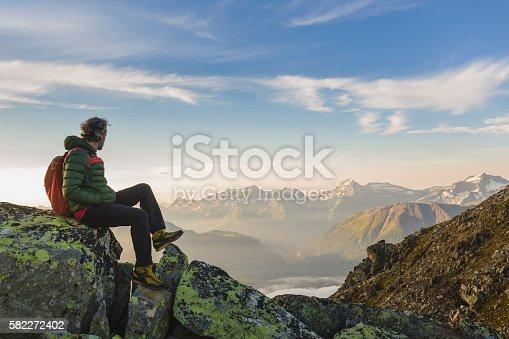 istock Hiker on top looks mountain panorama 582272402