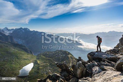 istock Hiker on top looks mountain panorama 582272468
