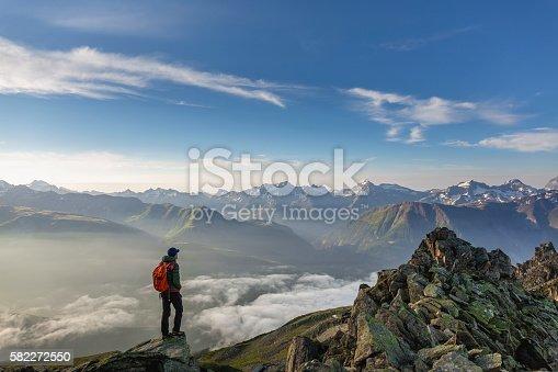 istock Hiker on top looks mountain panorama 582272550