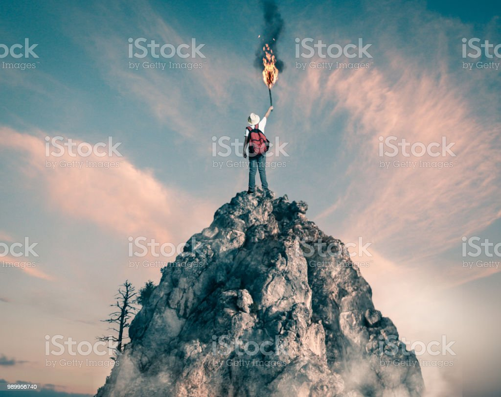 Hiker on top of a rocky mountain holding up a torch. stock photo