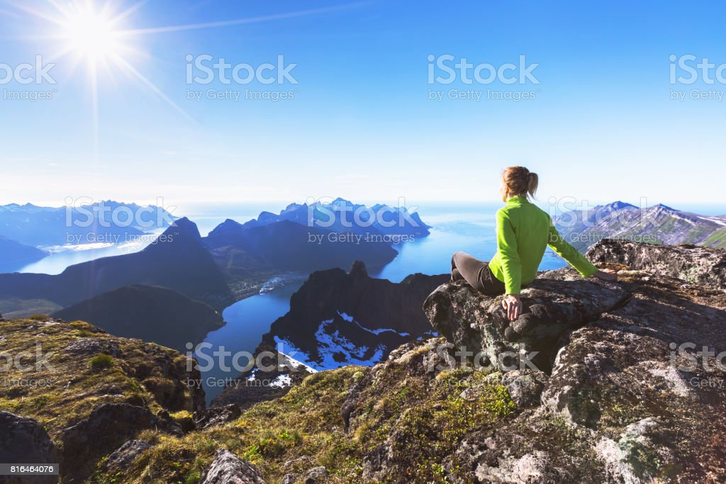 Hiker on top of mountain with view of norwegian fjord stock photo