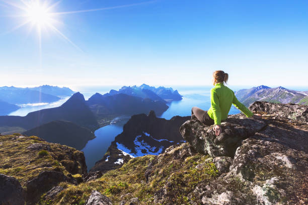 Hiker on top of mountain with view of norwegian fjord Woman hiker relaxing at the top of the mountain and looking at incredible views of a  Norwegian fjord on Senja Island, northern Norway lofoten stock pictures, royalty-free photos & images