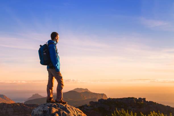 hiker on top of the mountain enjoying sunset stock photo