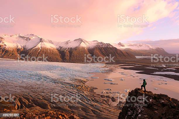 Photo of Hiker on Top of the Mountain Overlooking Skaftafell Glacier Iceland