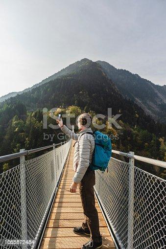 Man walking on suspension bridge between two mountain valleys