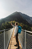 Hiker photographing with smartphone on the suspension bridge