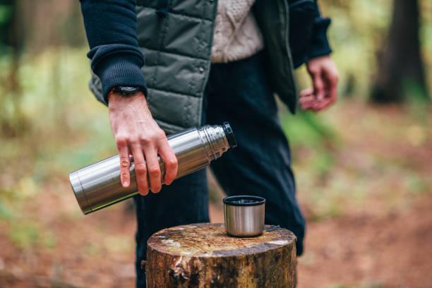 excursionista vertiendo bebida caliente - lifestyle color background fotografías e imágenes de stock
