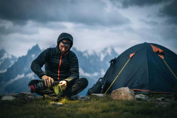 ハイカーは、高山キャンプ場でヘッドランプでホットドリンクを準備します - ダウンジャケット ストックフォトと画像