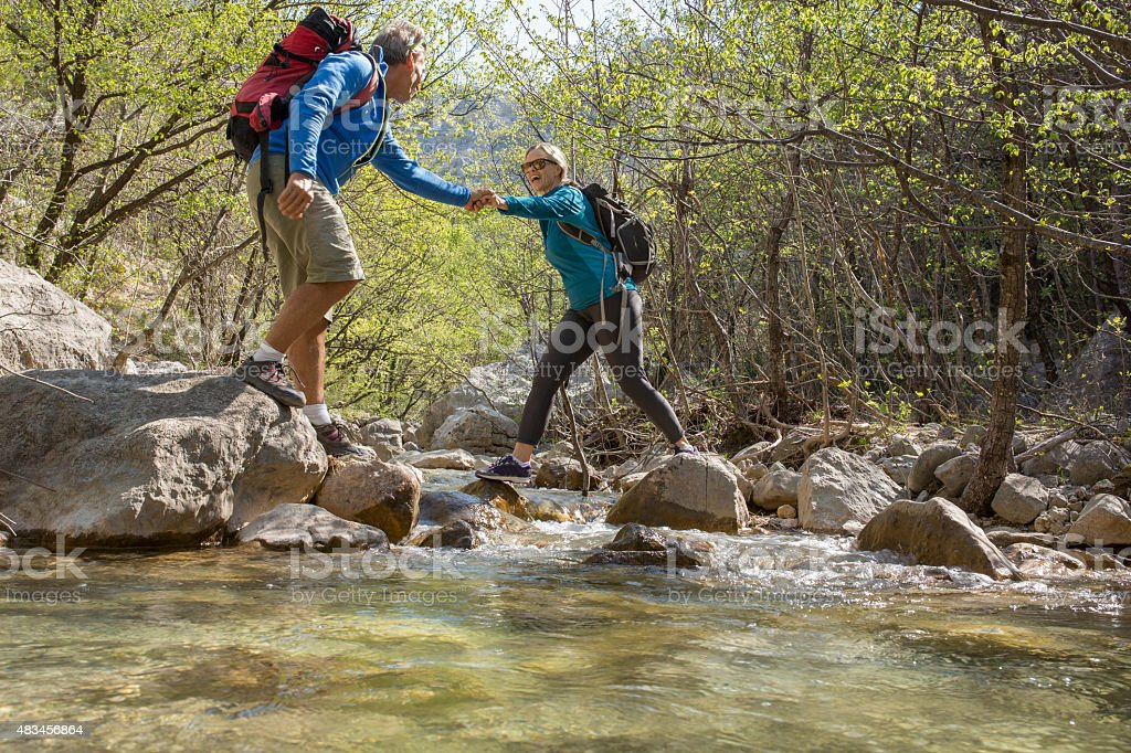 Hiker provides assistance to companion, in canyon stock photo