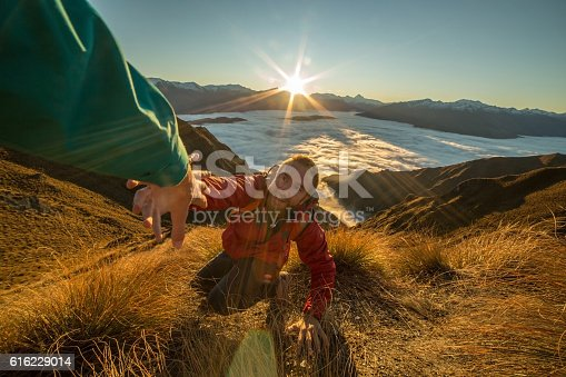 Young man pulling out his hand at the top of the mountain asking for help to reach the peak. Teammate offering a helping hand. New Zealand.