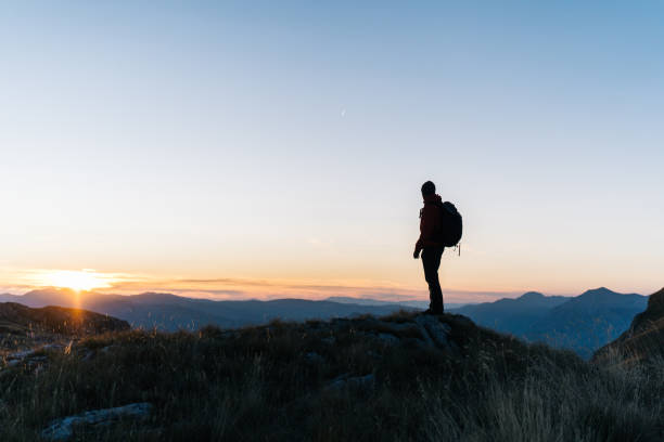 Hiker relaxes above mountain valley at sunrise stock photo