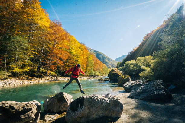 Hiker relaxes near autumnal river stock photo