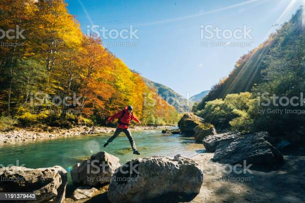 Photo of Hiker relaxes near autumnal river