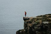 istock Hiker relaxes on coastal mountain cliff 1256427887