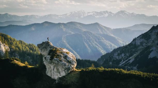 Hiker relaxes on mountain ridge at sunrise stock photo