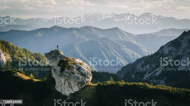 Photo of Hiker relaxes on mountain ridge at sunrise