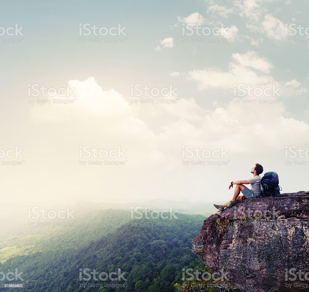 Hiker relaxing on the rock stock photo