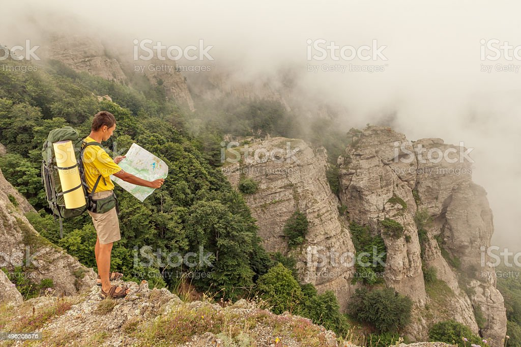 Hiker researches a way using a paper map stock photo