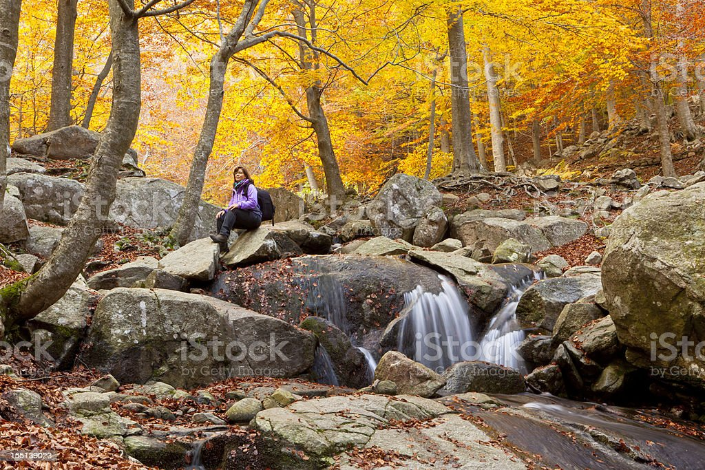 Hiker resting in autumn forest stock photo