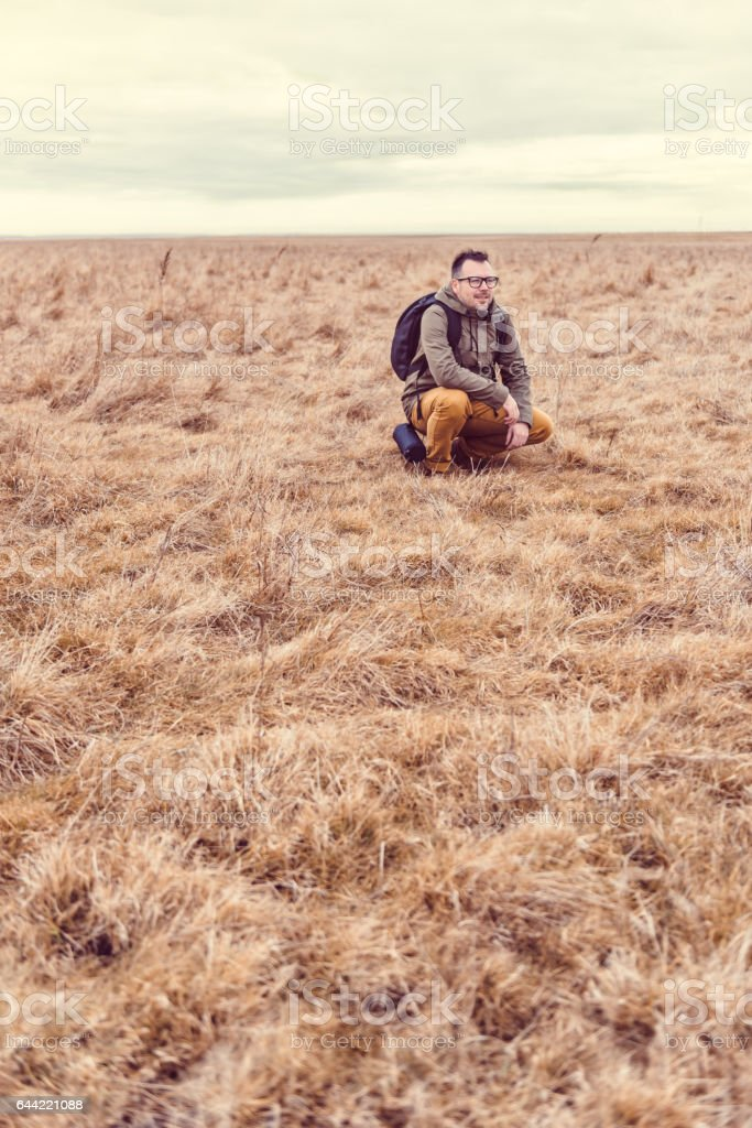 Hiker resting in grassland stock photo