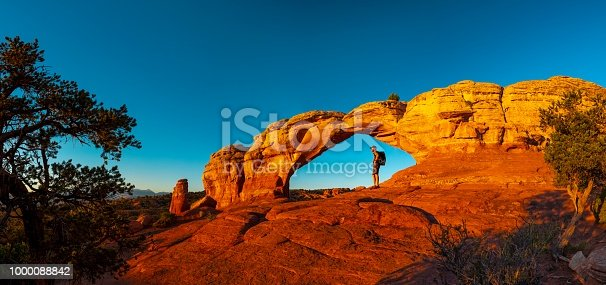 A hiker watching sunrise in Turret Arch, Arches National Park, Utah