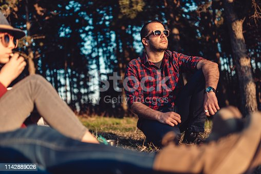 Hiker wearing plaid shirt and sunglasses resting on a grass by the pine forest with friends and enjoying looking at sunset