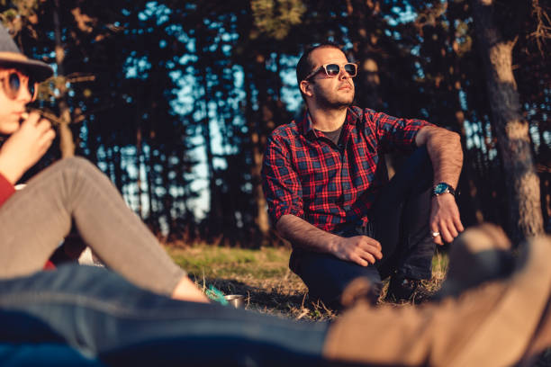 Hiker resting on a grass with friends and enjoying sunset Hiker wearing plaid shirt and sunglasses resting on a grass by the pine forest with friends and enjoying looking at sunset plaid shirt stock pictures, royalty-free photos & images