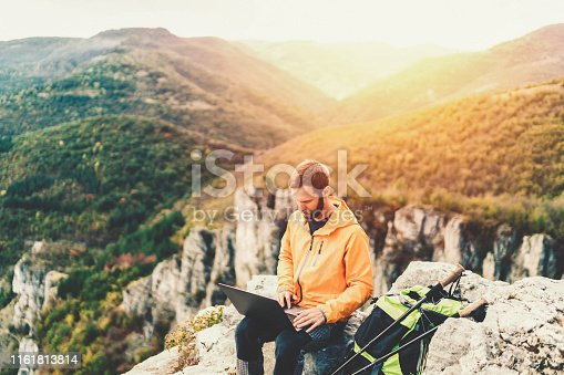 Hiker resting on the mountain top and using tablet