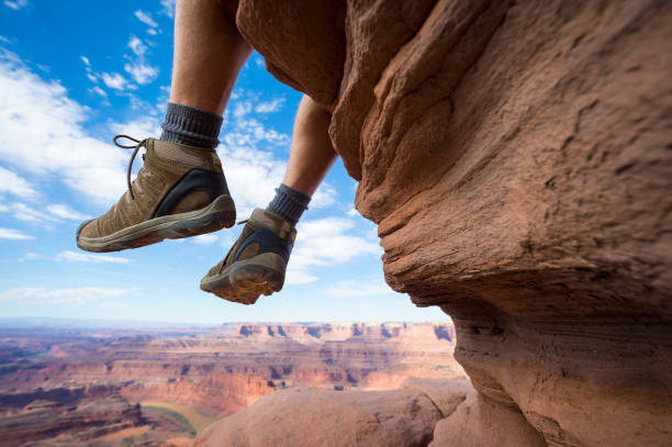 Hiker Resting with Boots Dancing Above Canyon stock photo