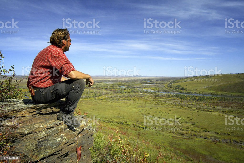 Hiker sat on mountain looking over panoramic view to blue royalty-free stock photo