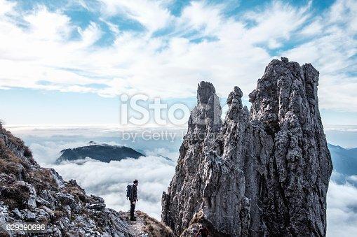 istock Hiker silhouette on peak of the mountain 629390696