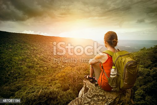 istock hiker sits on edge of the cliff and enjoying sunrise 487081194
