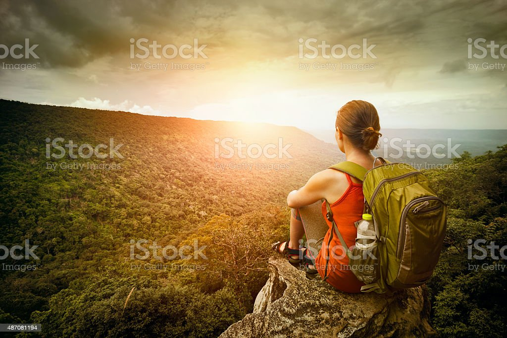 hiker sits on edge of the cliff and enjoying sunrise stock photo