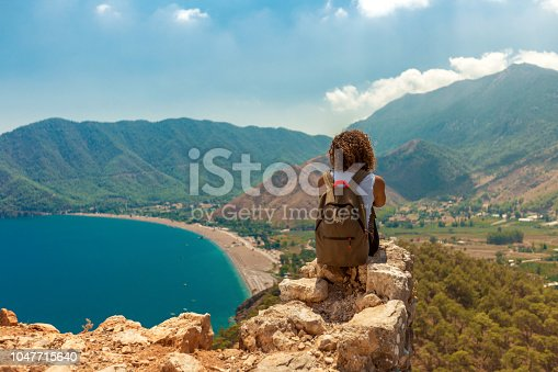 istock Hiker sits on edge of the cliff 1047715640